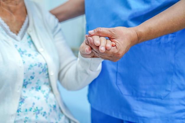 Aziatische verpleegkundige fysiotherapeut arts zorg, hulp en ondersteuning senior dame vrouw patiënt.