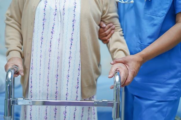 Aziatische verpleegkundige fysiotherapeut arts zorg, hulp en ondersteuning senior oude dame vrouw patiënt.