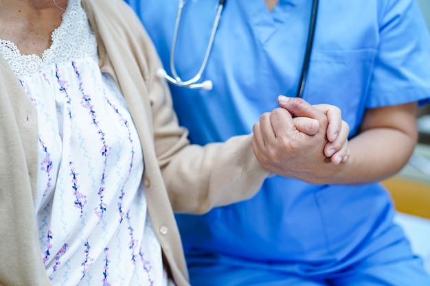 Aziatische verpleegkundige fysiotherapeut arts zorg, hulp en ondersteuning van senior of oudere oude dame vrouw