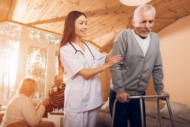 Aziatische verpleegster helpt man op een volwassen wandelaar in een verpleeghuis