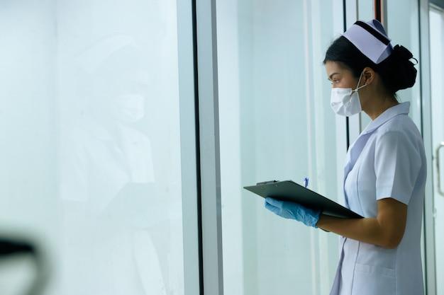 Aziatische verpleegster vrouw controleert de patiëntenkaart als routine, verpleegster kijkt door ramen buiten de zorgafdeling of eerste hulp in het ziekenhuis. gezondheidszorg gastvrijheid concept