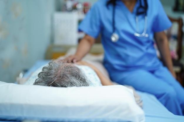 Aziatische verpleegsterszorg, hulp en steun hogere vrouwenpatiënt bij het ziekenhuis.