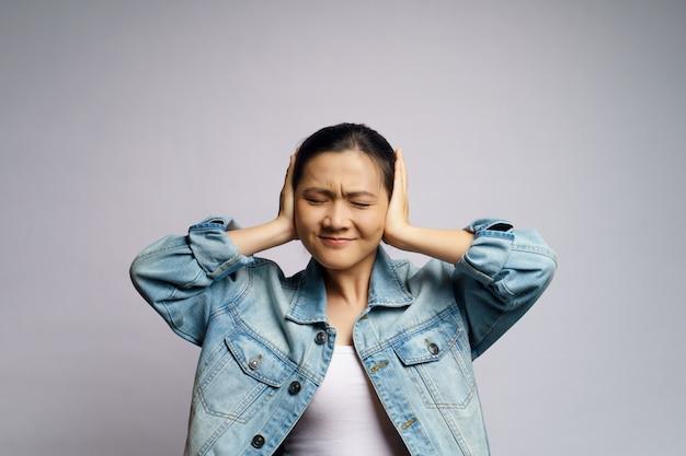 Aziatische verveelde en geïrriteerde vrouw, die haar geïsoleerde oren behandelt.