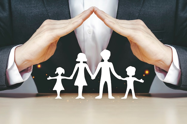 Aziatische verzekeringszakenlieden gebruiken hun handen om de witboekgezinnen te beschermen die thuis genieten.