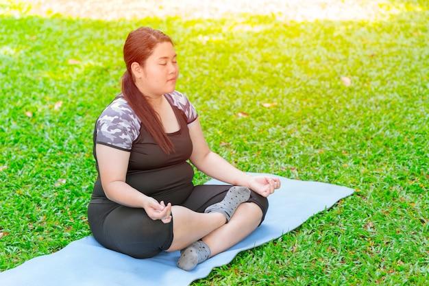 Aziatische vet plus grootte meisjeszitting yoga op mat in het groene tuinpark
