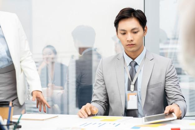 Aziatische vietnamese zakenman die projectdocumenten ernstig lezen op de vergadering