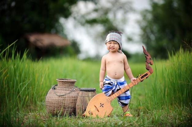 Aziatische vissende jongen die in het groene padieveld glimlachen voelen ontspannen ed.