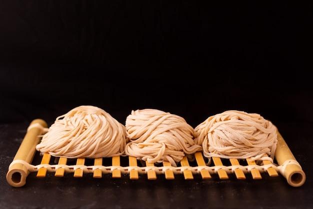 Aziatische voedsel concept zelfgemaakte uncook oosterse ei noedels op bamboe dienblad met kopie ruimte