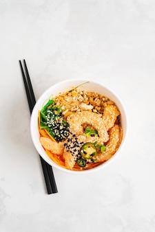 Aziatische voedselachtergrond met de kruidige kom van de garnalenpor met rijst, zeewieren en sesamzaden, avocado in een lunchdoos met eetstokjes op wit. gezonde zeevruchtenlunch. diëet voeding. bovenaanzicht met kopie ruimte.