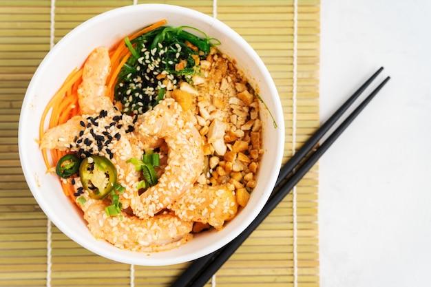 Aziatische voedselachtergrond met de kruidige kom van de garnalenpor met rijst, zeewieren en sesamzaden, avocado met eetstokjes op wit. boeddha schaal. gezonde zeevruchtenlunch. diëet voeding. bovenaanzicht met kopie ruimte.