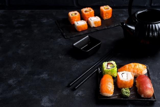 Aziatische voedselachtergrond met zwarte die ijzertheepot en sushi op leiplaat worden geplaatst op zwarte steenlijst