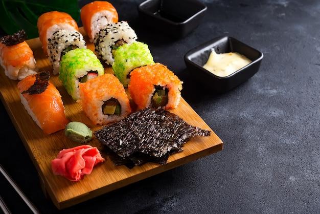 Aziatische voedselachtergrond met zwarte ijzertheepot en sushi die op houten plaat op zwarte steenlijst wordt geplaatst