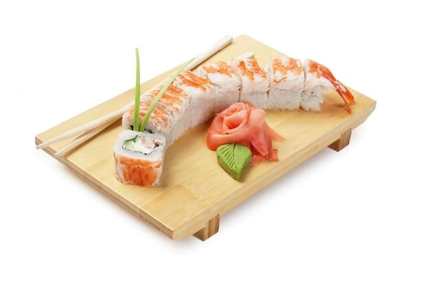 Aziatische voedselsushi op houten plaat die op witte ruimte wordt geïsoleerd