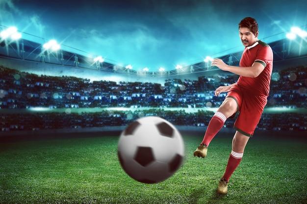 Aziatische voetbal speler schop bal