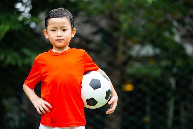 Aziatische voetbalkinderen bereiden zich voor op het trainen van voetbal.