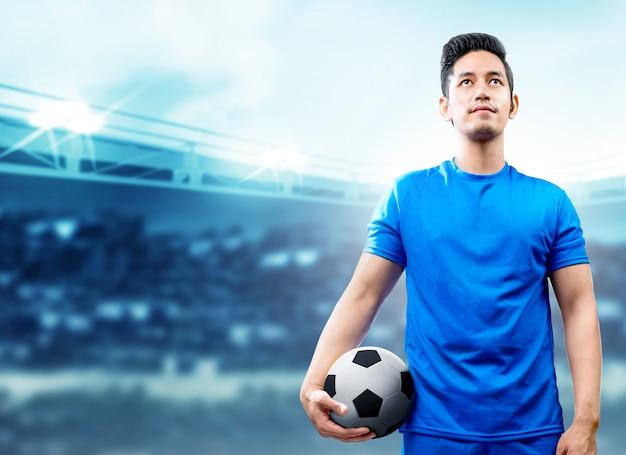 Aziatische voetbalstermens die in blauw jersey de bal op het voetbalgebied houdt