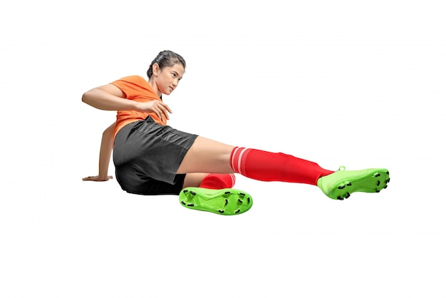 Aziatische voetbalstervrouw op glijdende uitrustingspositie