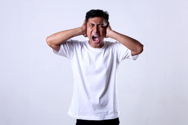 Aziatische volwassen man die een wit overhemd gebruikt terwijl hij schreeuwt terwijl hij zijn oren bedekt