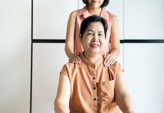 Aziatische volwassen vrouw blij met dochter, zorg en ondersteuning thuis, gelukkige oudere moeder van middelbare leeftijd, senior verzekeringsconcept