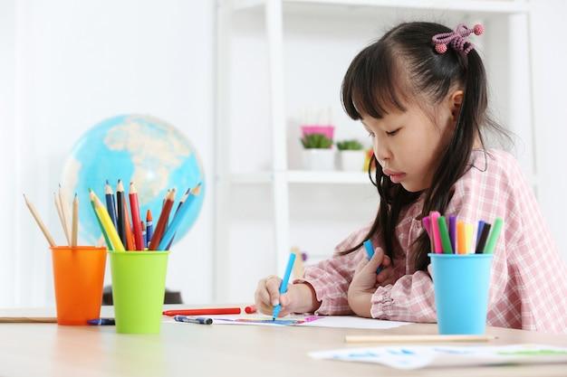 Aziatische voorschoolse student doet huiswerk door een kleur te tekenen
