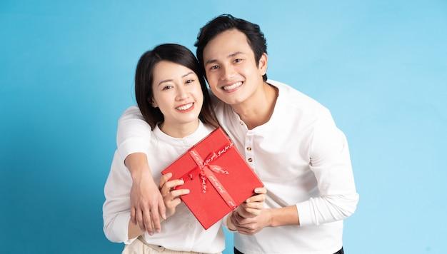 Aziatische vriend geeft geschenken aan zijn vriendin op valentijnsdag