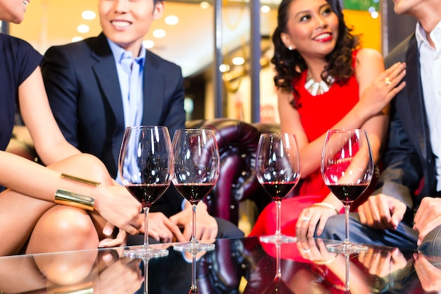 Aziatische vrienden chatten en rode wijn drinken