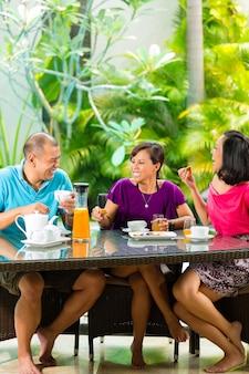 Aziatische vrienden die koffie op huisportiek hebben