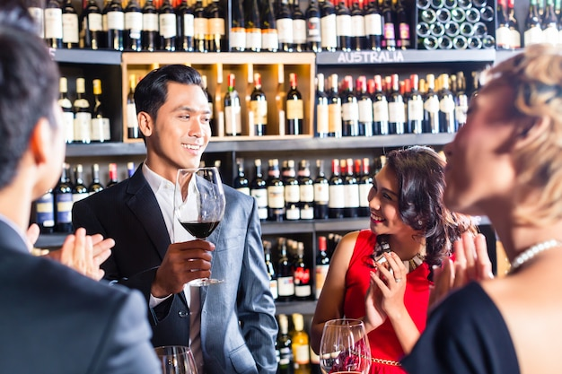 Aziatische vrienden die met rode wijn in bar roosteren