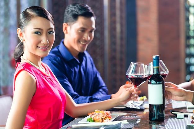 Aziatische vrienden die met wijn in restaurant roosteren