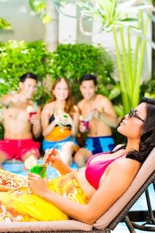 Aziatische vrienden feesten op zwembad feest in resort