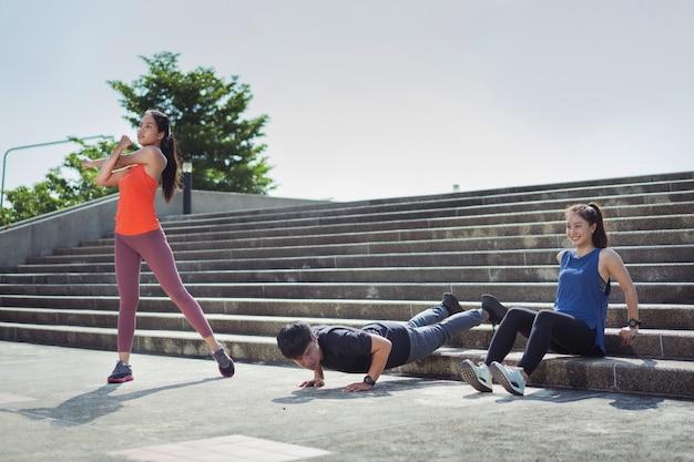 Aziatische vrienden groeperen joggen in de ochtend dat ze aan het opwarmen zijn en strekken