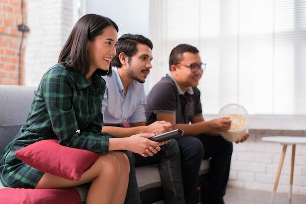 Aziatische vrienden kijken thuis tv. ze entertainen