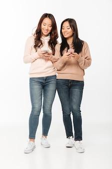 Aziatische vrij gelukkige dameszusters die door mobiele telefoons babbelen.