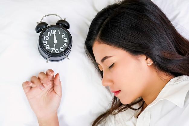 Aziatische vrij jonge meisjesslaap op bedruimte met wekker.
