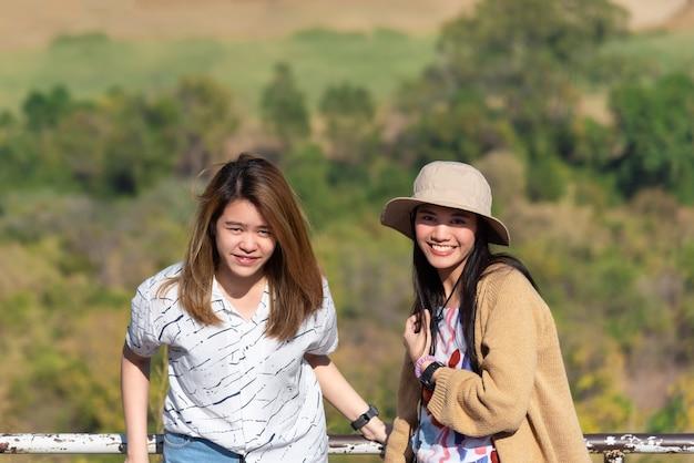Aziatische vrij leuke vrouwen met hoed ontspannen bij het landschapsgezichtspunt van de kuststad op berg