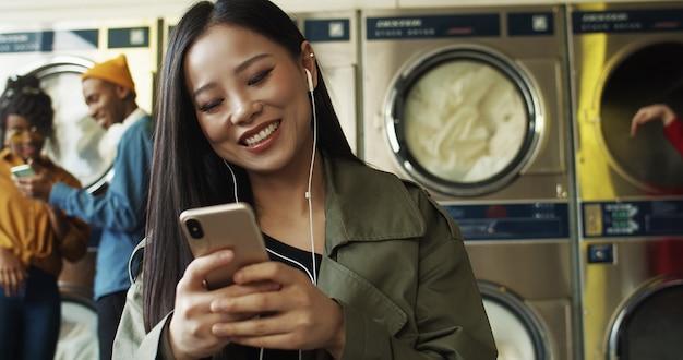 Aziatische vrij vrolijke vrouw die in hoofdtelefoons video op smartphone in de ruimte van de wasserijdienst letten op. mooi gelukkig meisje die aan muziek op telefoon luisteren en op kleren wachten om in washuis schoon te worden.