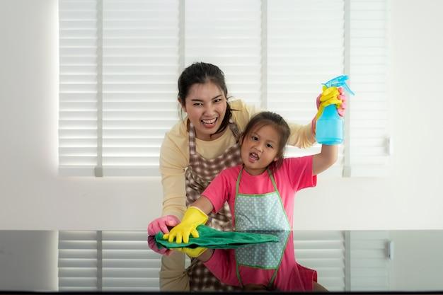 Aziatische vrolijke moeder en dochter schoonmakende lijstoppervlakte met vod en nevelfles samen
