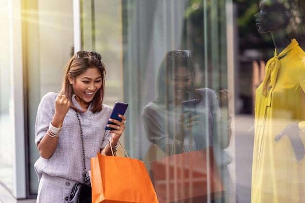 Aziatische vrolijke vrouw bij het gebruik van de slimme mobiele telefoon voor online chequeboek is