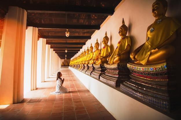 Aziatische vrouw aan het respecteren van het standbeeld van boedha in ayutthaya, thailand.