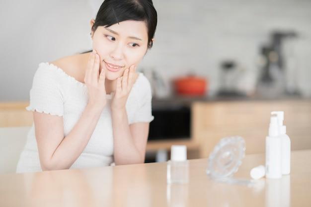 Aziatische vrouw aanraken en controleren van haar huid in de kamer