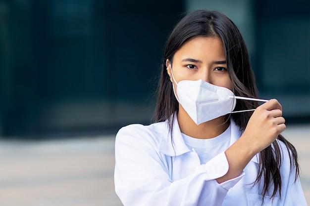 Aziatische vrouw, aantrekkelijk etnisch meisje in medisch masker op haar gezicht camera kijken met een serieuze blik in wit overhemd buiten business center