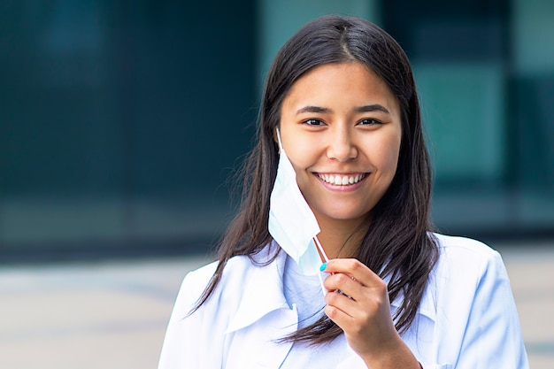 Aziatische vrouw, aantrekkelijk etnisch meisje neemt het medische masker van haar gezicht af, kijkt blij met een glimlach naar de camera. in een wit overhemd buiten het zakencentrum.