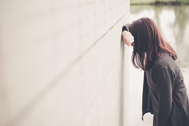Aziatische vrouw alleen en gedeprimeerd zitten, portret van vermoeide jonge vrouw. depressie