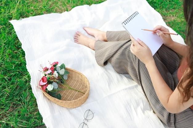 Aziatische vrouw alleen rustend op een picknick in natuurpark buiten op zonnige dag genieten van zomer en dromen