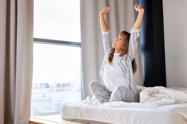 Aziatische vrouw armen strekken na het wakker worden in de ochtend, zittend op bed met opgeheven armen, glimlach