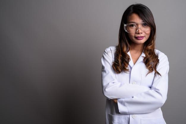 Aziatische vrouw arts beschermende bril tegen grijze backg