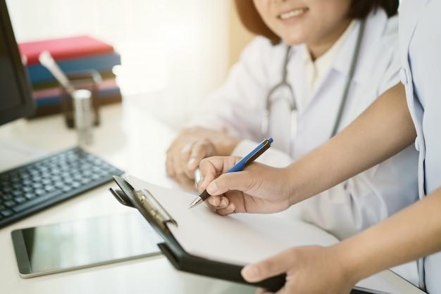Aziatische vrouw arts en verpleegster in het ziekenhuis die administratie in ruimte doen.