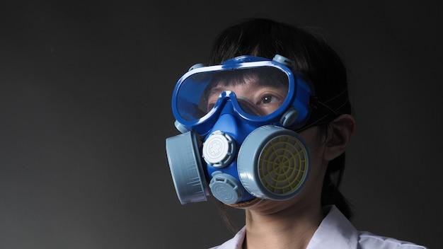 Aziatische vrouw arts in een chemisch beschermend medisch masker en een veiligheidsbril.