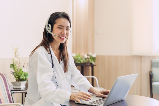 Aziatische vrouw arts in hoofdtelefoon die het online oproepen van haar hoofdtelefoonmicrofoon voor een pijnpatiënt neemt