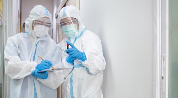 Aziatische vrouw arts in persoonlijk beschermend kostuum met masker die op quarantainepatiëntgrafiek schrijven